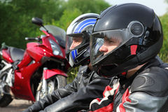 Closeup of two motorcyclists sitting near bikes Stock Photography