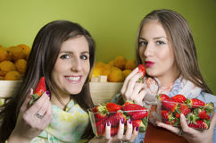 Closeup of two natural, beautiful girls eating strawberries Royalty Free Stock Image