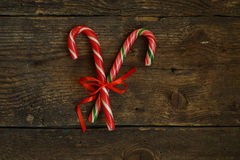 Closeup of two old fashioned candy canes on a rustic wooden back Royalty Free Stock Images