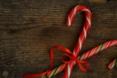 Closeup of two old fashioned candy canes on a rustic wooden back Stock Image