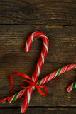 Closeup of two old fashioned candy canes on a rustic wooden back Royalty Free Stock Photography