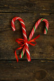 Closeup of two old fashioned candy canes on a rustic wooden back Royalty Free Stock Photo