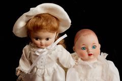 Closeup of two old porcelain dolls on black background royalty free stock image