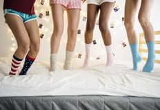 Closeup of two pairs of legs with socks jumping on the bed Stock Photos