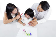 Closeup of two parents teach their kid to learn Royalty Free Stock Image