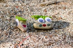 Closeup of two rocks painted with googly eyes on a ground royalty free stock photography