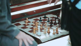 Closeup of two senior men playing chess at park. Sitting on bench stock video footage