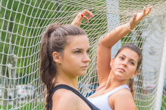 Closeup of two sporty girls posing at a football grid. Close-up, posing sports girls football grid Stock Photo
