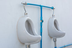 Closeup of two white urinals in men's bathroom Stock Image