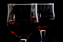 Closeup of Two Wineglasses Filled With Red Wine on Black Stock Images