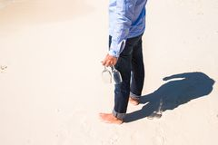 Closeup of two wineglasses in a man's hand on the white sandy beach Royalty Free Stock Photo