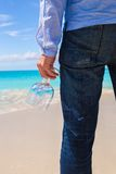 Closeup of two wineglasses in a man's hand on the white sandy beach Royalty Free Stock Photography