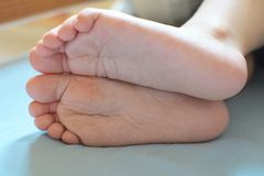 Child feet on light blue bed sheet stock image