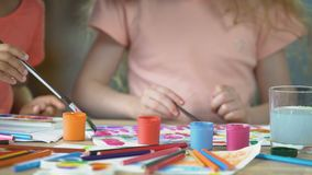 Closeup of two young girls painting a picture at preschool art club, hobby. Stock footage stock video footage