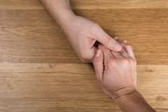 Closeup on two young lovers holding hands at a table stock photos