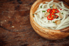 Closeup of udon noodle in wood bowl on wooden floor Royalty Free Stock Photos