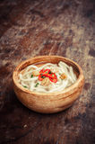 Closeup of udon noodle in wood bowl on wooden floor Royalty Free Stock Image