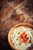 Closeup of udon noodle in wood bowl on wooden floor Royalty Free Stock Images