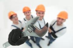 closeup uma equipe dos construtores que mostram uma chave de tubulação foto de stock