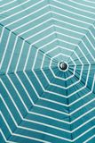 Closeup of an umbrella with white stripes on sky blue color royalty free stock image