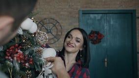 closeup Una bella giovane donna allegramente decora un albero di Natale con il suo marito Una famiglia felice Natale video d archivio