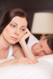 Closeup of unhappy woman lying in bed stressed. Stock Image