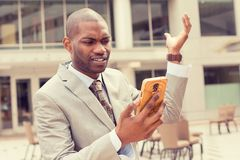 Closeup unhappy young man in suit talking texting on cellphone outdoors. Negative human face expression Royalty Free Stock Image