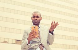 Closeup unhappy young man in suit talking texting on cellphone outdoors. Negative human face expression Royalty Free Stock Photography