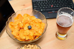 Closeup of unhealthy snack and beer with laptop in background Stock Photography
