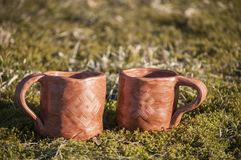 Closeup of unique handmade two cups with folk signs on green moss in summer sunset sunlight before kiln. Baltic black pottery of clay royalty free stock photos