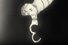 Closeup of unlocked handcuffs hanging on man hand Royalty Free Stock Image