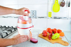 Closeup. Unrecognizable man presses carrot inside juicer to make tasty juice for breakfast from fresh vegetables, pours in transpa Royalty Free Stock Photography
