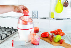 Closeup. Unrecognizable man presses tomatoes inside juicer to make tasty juice for breakfast from fresh vegetables, pours in trans Royalty Free Stock Image