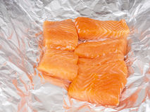 Closeup of unseasoned salmon pieces. In aluminum foil Royalty Free Stock Photos