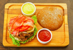 Closeup up of a delicious hamburger with beef, onion, tomato, lettuce and cheese on wooden board, above view.  Royalty Free Stock Photo