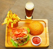 Closeup up of a delicious hamburger with beef, onion, tomato, lettuce and cheese on wooden board, above view.  Stock Photography