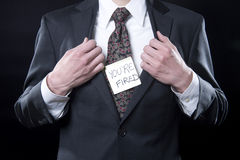 Fired!. Closeup up executive with hands on lapels and   Your're Fired sticky note Royalty Free Stock Photos