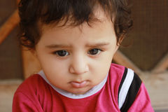 Closeup-up portrait headshot of a adorable sad boy thinking. Sadly, wearing pink cloths Royalty Free Stock Photos
