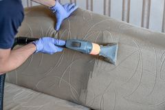 Closeup of upholstered Sofa chemical cleaning. With professionally extraction method. Man is holding nozzle royalty free stock image