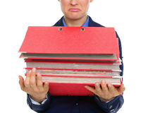 Closeup of upset businesswomans hands holding stack of folders Stock Photo