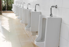 Closeup urinals white color in men`s public restroom with light Royalty Free Stock Photos