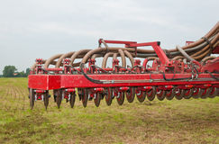 Closeup of a used manure injector (front). With a field in the background Stock Images