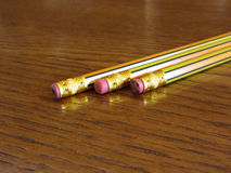 Closeup of used pencil erasers on wooden table Royalty Free Stock Image