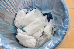 Closeup used sanitary napkin pad wrapped disposed in rubbish bin Stock Image