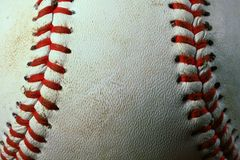 Closeup of a used white baseball with red seams. stock image