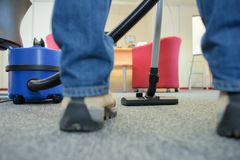 Closeup vacuum and feet person using it Royalty Free Stock Photography