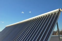 Closeup of vacuum solar water heating system on the house roof against blue sky. Energy saving concept. Royalty Free Stock Photo