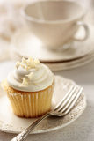 Closeup of vanilla cupcake with tea cup Stock Image
