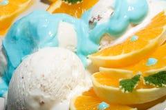 Closeup of vanilla ice cream dessert. Scoops of vanilla ice cream and sliced orange served by Blue Curacao syrup stock photos