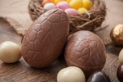 Various chocolate easter eggs on wooden background. Closeup of various chocolate easter eggs on wooden background Royalty Free Stock Image